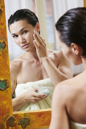 Woman Putting on Facial Cream LANG_EVOIMAGES