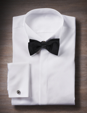 cuff: White, tuxedo shirt with a bow tie and cuff link, studio shot on wooden background LANG_EVOIMAGES