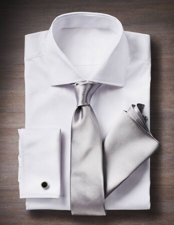 White shirt with a tie, handkerchief and cuff link, studio shot on wooden background