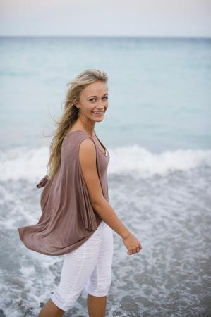 Woman Walking Through Surf on Beach
