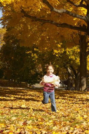 exhilarating: Girl Running through Leaves LANG_EVOIMAGES