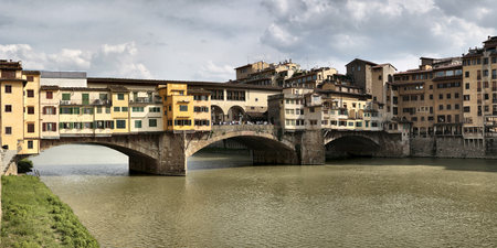 incidental people: Ponte Vecchio, Medieval bridge crossing the Arno River, now used for art dealers and jewellry stores, Florence, Italy