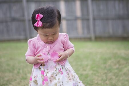Toddler Girl Frowning as she Opens an Empty Easter Egg