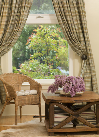 Chair and Coffee Table with Flowers by Window with Drapes in Living Room