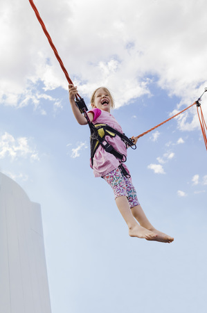 tied in: 6 year old girl jumping with a bungee trampoline on a sunny day, Germany