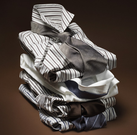 Stack of mens, striped dress shirts with ties on brown background
