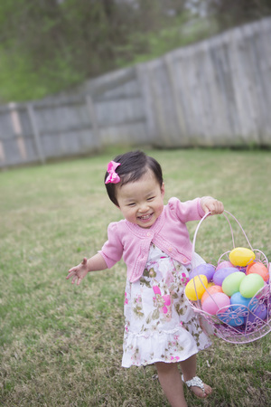 Toddler Girl Running and Smiling with Full Easter Egg Bakset