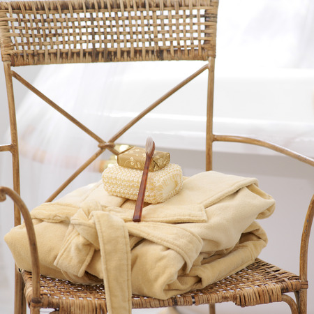 Folded Robe with Soap, Loofah and Toothbrush on Wicker Chair