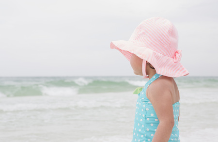 Portrait of Toddler Girl wearing Sunhat on Beach and Looking out at Ocean, Destin, Florida, USA