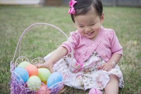 Portrait of Toddler Girl wearing Pink and Sitting on Grass with Easter Basket in Backyard