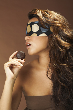 Woman With Blindfold Holding Chocolate