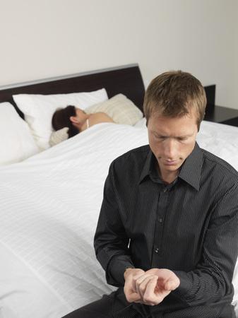 Man Getting Dressed, Woman Sleeping LANG_EVOIMAGES