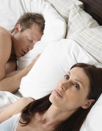 Woman Lying Awake in Bed while Man Sleeps