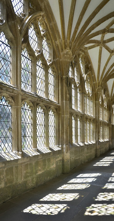 lattice window: View of sunlit passage with light from windows creating shadows on the floor at Wells Cathedral in Somerset, England