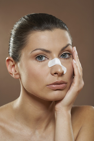 Portrait of Woman with Bandage on Nose LANG_EVOIMAGES