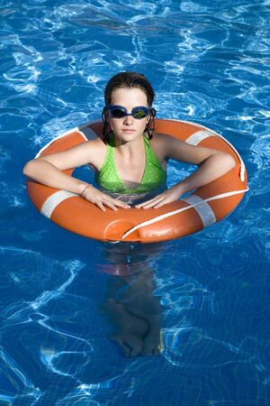 Girl in Swimming Pool With Life Preserver LANG_EVOIMAGES