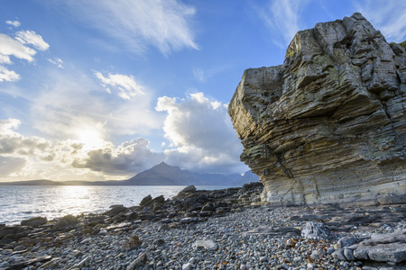 Rock face of sea cliff with honeycomb weathering and sun shining over Loch Scavaig, Isle of Skye in Scotland, United Kingdom
