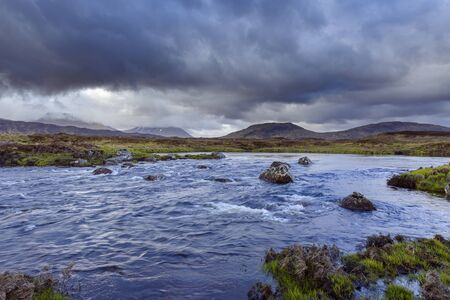 River in moor landscape with dark storm clouds with mountains in the background at Rannoch Moor in Scotland, United Kingdom LANG_EVOIMAGES