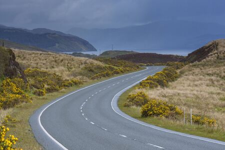 Winding country road with an overcast sky in springtime in the Isle of Skye, Scotland, United Kingdom LANG_EVOIMAGES