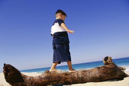 Boy Walking on Log at Beach LANG_EVOIMAGES