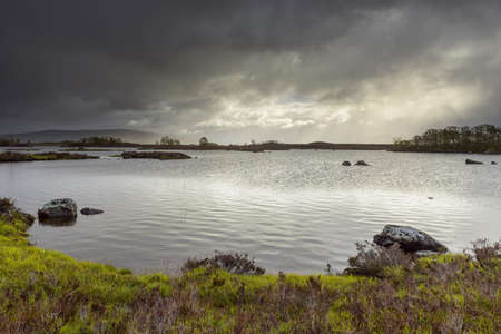 Shoreline of a lake in a moor landscape with stormy sky at Rannoch Moor in Scotland, United Kingdom LANG_EVOIMAGES