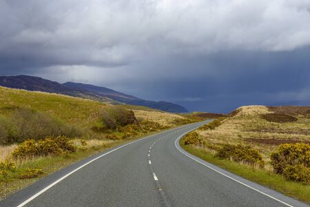 Winding country road with rainclouds in springtime on the Isle of Skye in Scotland, United Kingdom