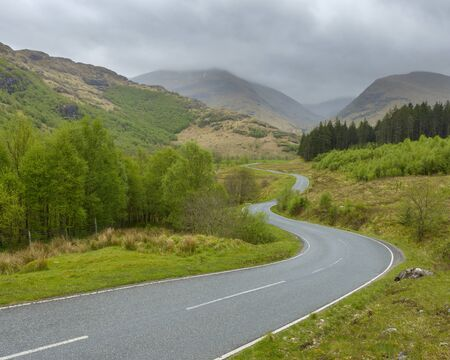 Winding country road and hills with overcast sky at Glen Nevis near Fort William in Scotland, United Kingdom