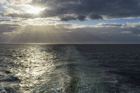 Ships wake with sun shining through the clouds over the North Sea, United Kingdom LANG_EVOIMAGES