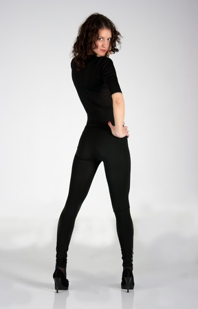 Adult young woman in black clothes posing in the studio