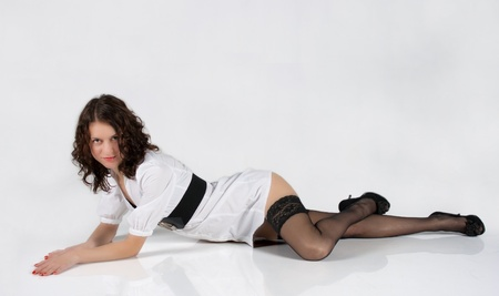 Woman in white dress and black shoes posing lying in the studio on light background Standard-Bild