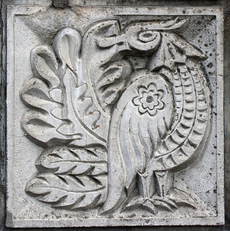 old bas-relief of fairytale fantasy bird on the wall Stock Photo
