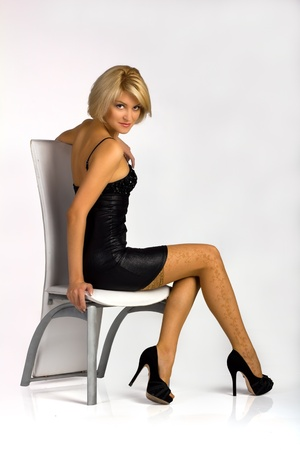 young girl in black little dress and stockings sitting on the chair in studio