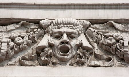 heads old building facade: bas-relief mans face on the wall of city street