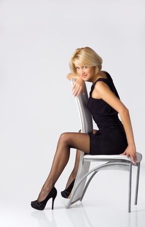 young blondie girl in black dress and stockings posing sitting on the chair Stock Photo - 9948247
