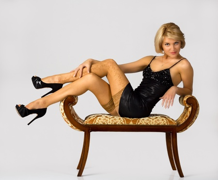young girl in black little dress and stockings lying on the banquette in studio