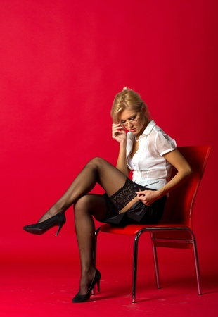 sexy woman teacher correcting black stockings sitting on the chair