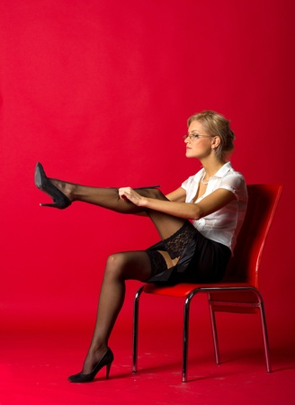 sexy woman teacher correcting black stockings sitting on the chair in studio