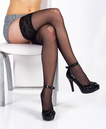 slim sexy legs in black stockings and shoes in studio