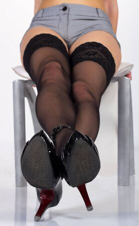long slim sexy legs in black stockings and shoes in studio