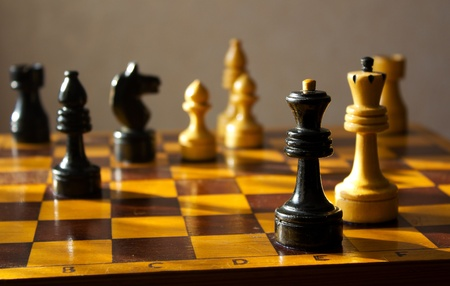 situation on chessboard with black queen and white king photo