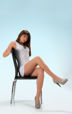 pretty girl in light dress and shoes posing sitting in studio photo