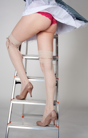 beautiful long female legs staying on the stairway in studio