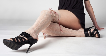 beautiful long female legs in light stockings and black shoes sitting in studio