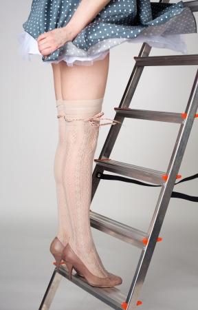 beautiful slim female legs staying on the stairway in studio Stock Photo - 14317877