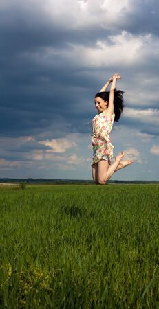 young girl jumping on the field on sunny summer day
