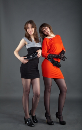 two young pretty girls posing staying in studio