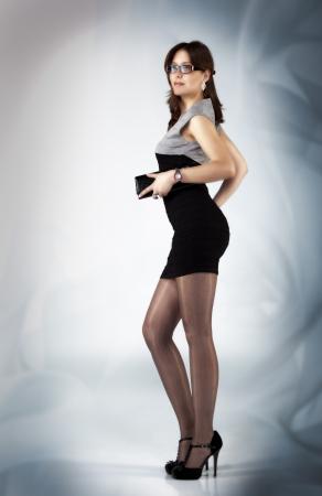 pretty girl in black dress posing standing in studio Stock Photo