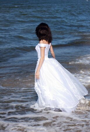 young girl in white dress on the seashore on summer photo