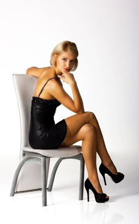 young woman in a black dress posing sitting on a chair in studio