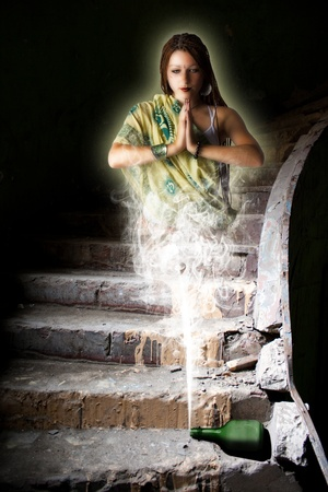 fabulous girl genie out of the bottle in an abandoned dark room photo